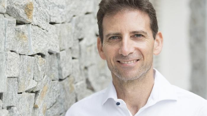 Headshot of Serge Benhayon standing alonside a brick paved wall