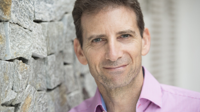 Headshot of Serge Benhayon leaning up against a rock wall